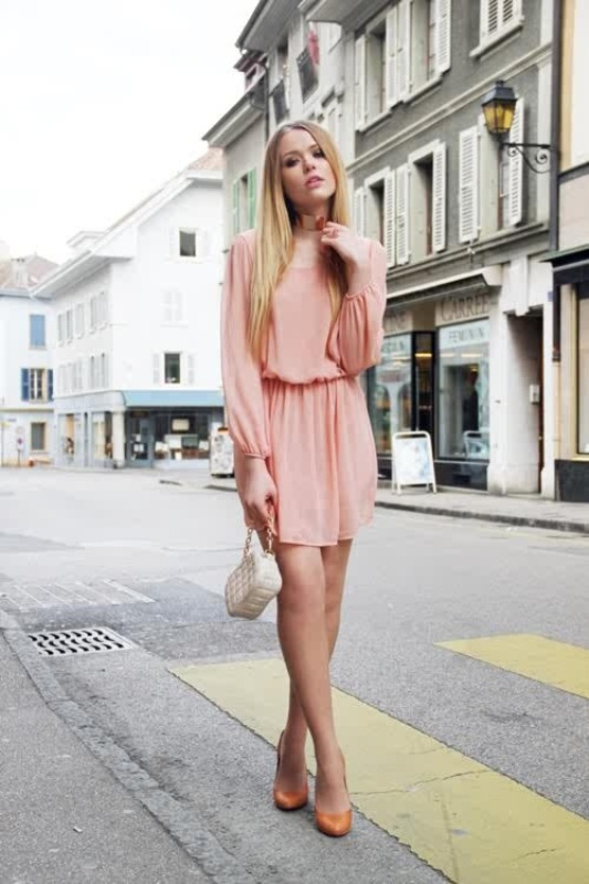 a blush mini dress with a highlighted waist, light pleating on the sleeves and skirt, a necklace, orange shoes and a neutral bag for a spring wedding