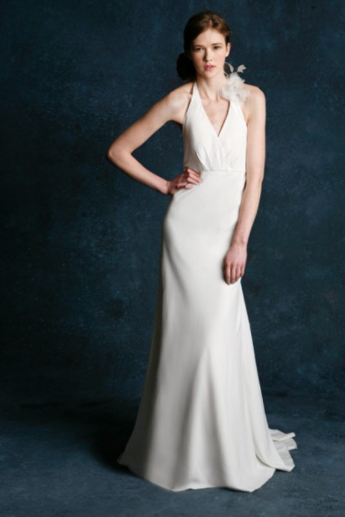a plain sheath wedding dress with a halter neckline and a feather clip to make it stand out
