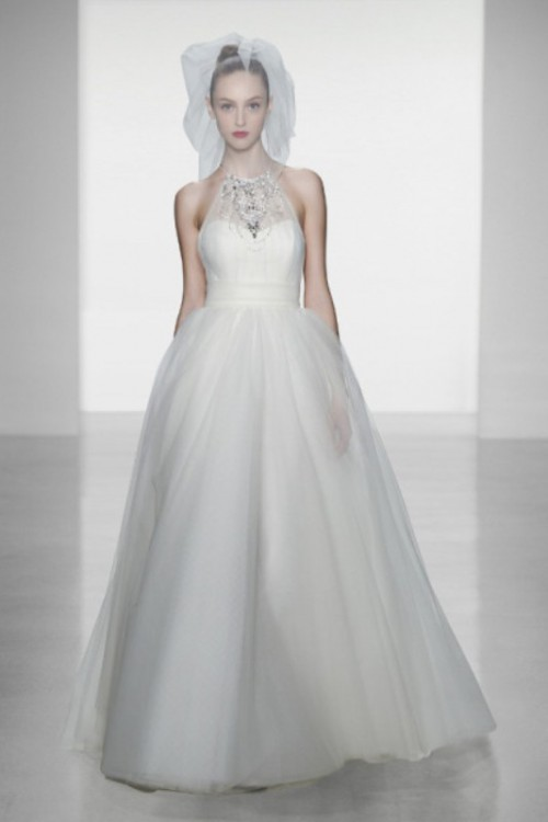 a princess-style wedding dress with an embellished halter neckline, a full skirt and a birdcage veil