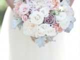 a pastel wedding bouquet of blush, lilac and white blooms and pale greenery for a spring or summer wedding