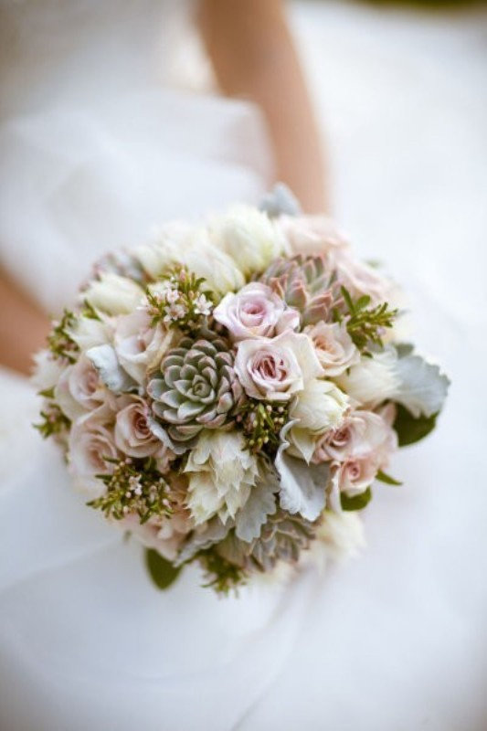 a pastel wedding bouquet of neutral and blush blooms and some pale greenery and succulents