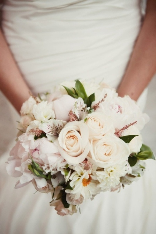 a pretty pastel wedding bouquet of blush and white blooms and some greenery plus textural elements