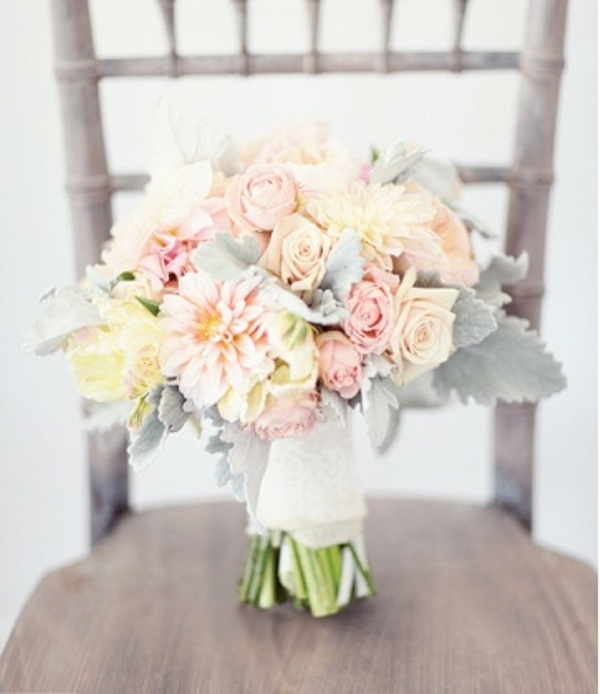 a pastel wedding bouquet of blush, neutral and peachy blooms and pale greenery