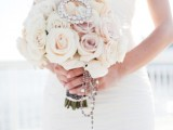 a glam neutral and blush rose wedding bouquet with a rhinestone detail and rosary hanging down