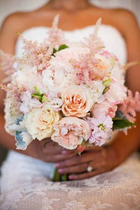 a pastel wedding bouquet of peachy, blush and neutral blooms and some greenery for a spring or summer wedding