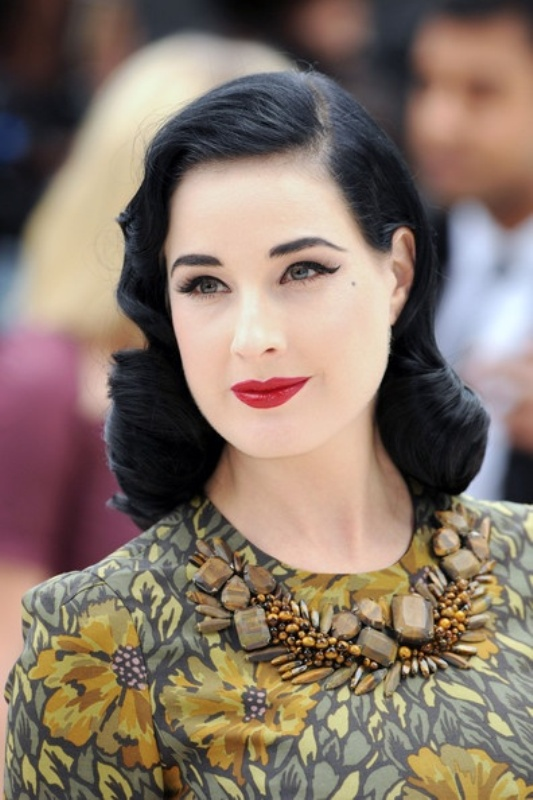 middle length black hair with vintage curls looks perfectly stylized and very accenting and bold