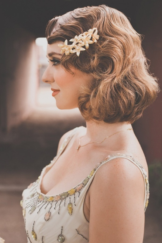 vintage Hollywood waves on short hair looks very chic and elegant and a flower hairpiece brings a feminine feel
