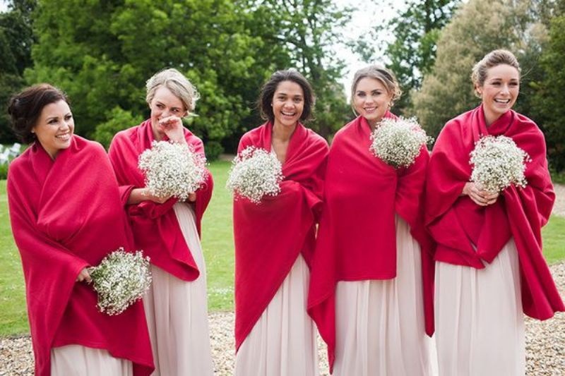 bright red coverups keep the bridesmaids warm and add color to their looks