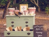 a fun retro-inspired popcorn bar with a vintage dresser, colorful striped popcorn buckets, paper bags and a chalkboard sign
