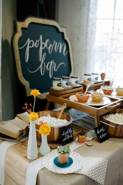 a rustic popcorn bar with burlap and paper on the table, wooden baskets with popcorn and stands with condiments and sprinkles