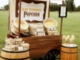 a rustic meets vintage popcorn bar with a wagon with popcorn in wooden baskets and barrels with more sweets around
