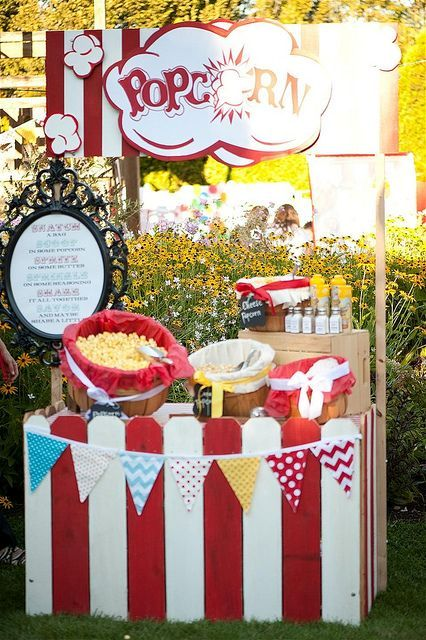 a fun retro popcorn bar with a table surrounded with red and white planks, a colorful garland and sign, colorful wood baskets with popcorn
