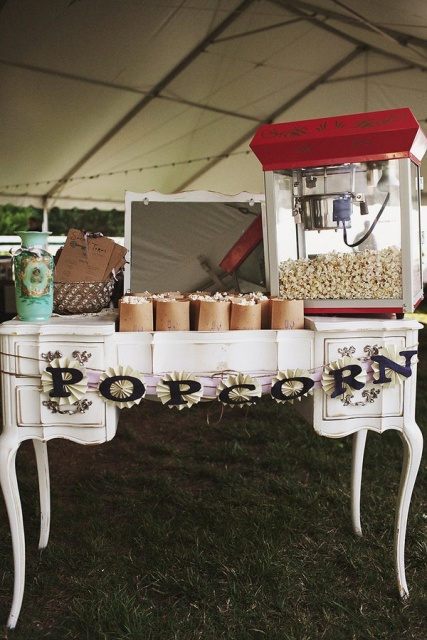 a vintage-inspired popcorn bar with an elegant table, a paper garland, a mirror and popcorn machine plus paper bags