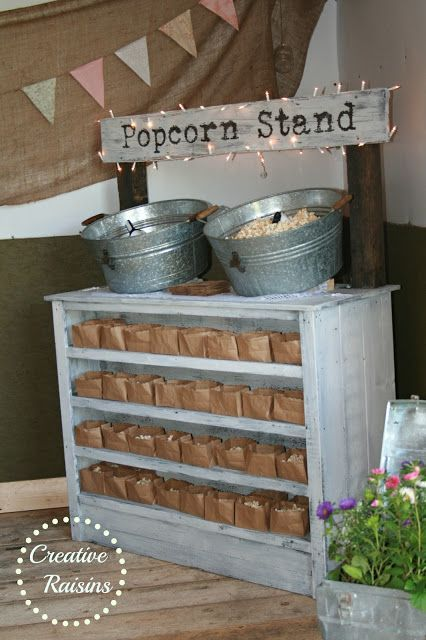 a rustic popcorn stand with a whitewashed cabinet with paper bags with popcorn, buckets with popcorn and a sign highlighted with lights