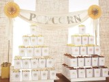 a simple and rustic popcorn bar with a stained table and stands with usual and chocolate popcorn in paper bags and a garland over it