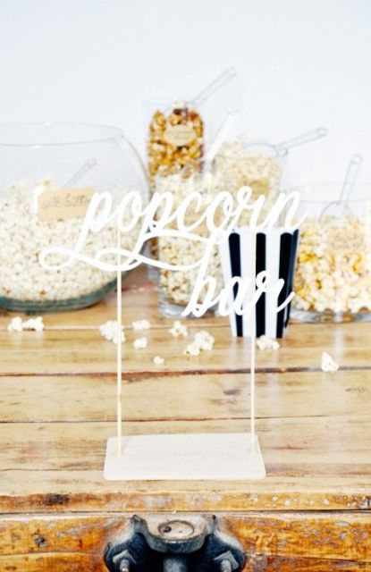 a simple and modern popcorn bar with a sign, glass bowls and jars with popcorn and striped paper bags
