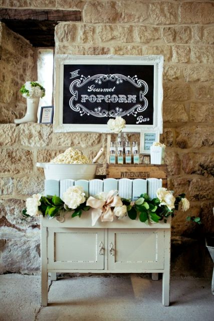 a simple rustic popcorn bar with  a vintage cabinet dressed up with a lush greenery and bloom garland with a bow, a bucket with popcorn, condiments and paper bags