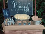 a vintage rustic popcorn bar with a trolley covered with kraft paper, popcorn in a bucket, paper bags and a large chalkboard sign