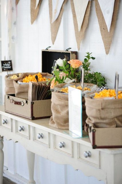 a rustic popcorn bar done with a vintage console table, suitcases and burlap sacks withh popcorn