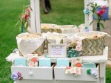 a simple popcorn bar with a vintage dresser that features woven baskets with popcorn and paper bags to store it plus some blooms