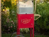 a red vintage-inspired popcorn automate on wheels is a fun idea to give a cool vintage touch to your wedding