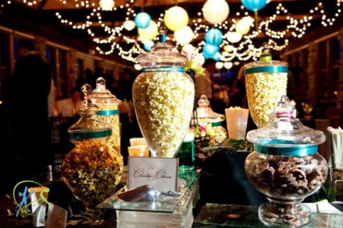 an elegant popcorn bar done with glass jars with lids and signage to mark each type