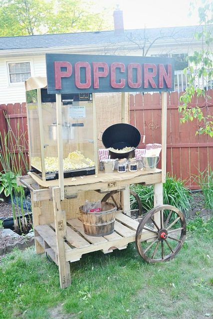 a rustic vintage popcorn bar with a vintage wagon, a popcorn machine, a bucket with popcorn and paper bags to serve it