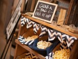 a small rustic popcorn bar with chevron covered baskets is a cool idea of a late night snack