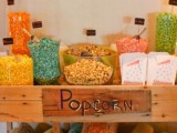 a fun and bright popcorn bar made of a wagon on wheels, with colorful popcorn in glass bowls and in sacks
