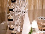 a creative wheel popcorn bar with popcorn bowls on the wheel to rotate and various sweets on the table