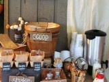 a rustic popcorn bar with wooden signage, boxes, a kettle, cups and a wooden basket with popcorn plus paper bags