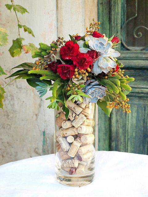 a bright floral arrangement with wine corks placed inside is a stylish wedding centerpiece idea