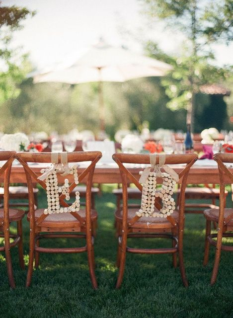 wine cork monograms hanging on wedding chairs are a cool idea to personalize the chairs instead of usual signs