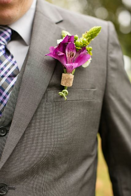 a bright wedding boutonniere of a wine cork piece and bright pink and green blooms looks chic