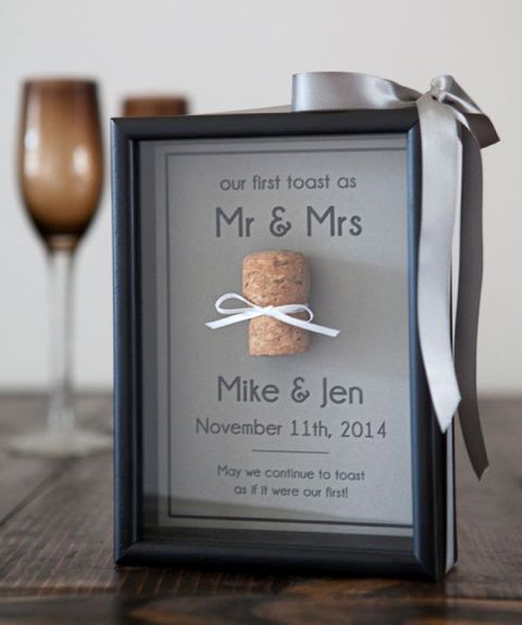 the couple's first toast and a wine cork attached in the frame - a cork from that bottle
