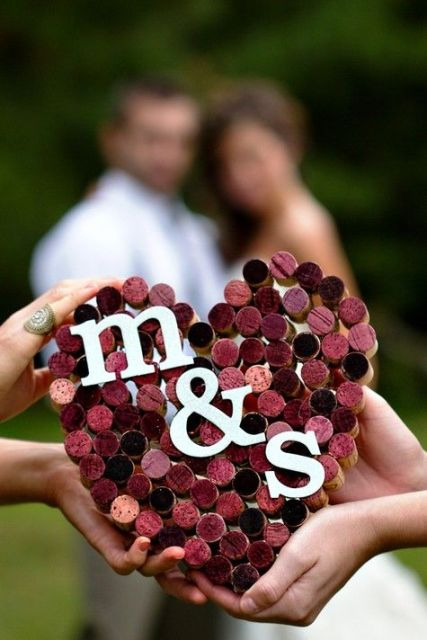 a purple wine cork wedding heart with monograms as a decoration for a bold and cool touch in your venue