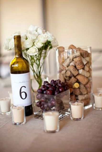 a wedding centerpiece of grapes, wine corks, a wine bottle with a number and white blooms