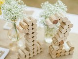 table numbers made of wine corks, with baby's breath arrangements will make your table natural and cute