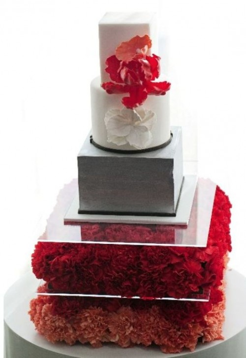 a grey and white wedding cake with white and red sugar blooms served on a pillow of red blooms