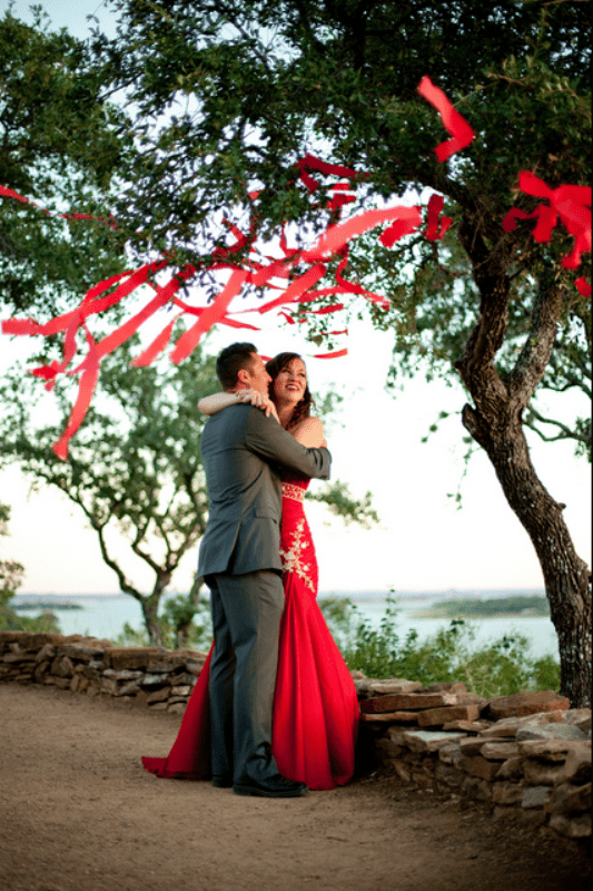 a groom wearing a grey suit, a bride wearing a red wedding gown for a red and grey winter wedding