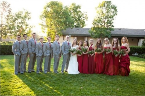 groomsmen wearing grey suits with red ties and bridesmaids wearing red maxi dresses