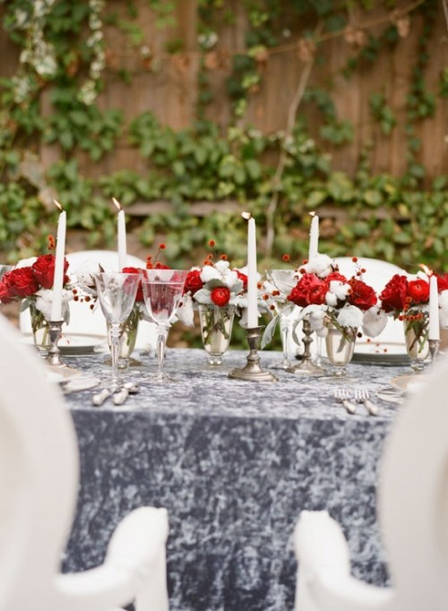 a grey marbleized table runner and bold red and white floral centerpieces plus tall candles
