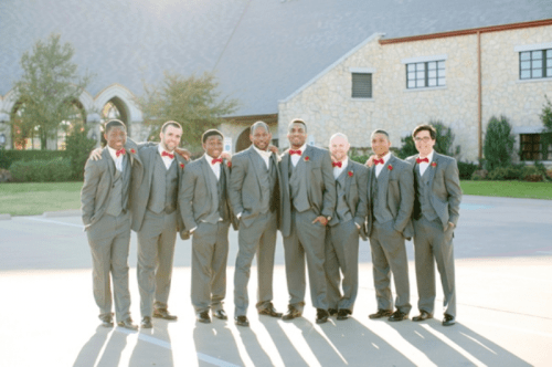 grey three-piece suits and red bow ties and boutonnieres are amazing for a fall or winter wedding
