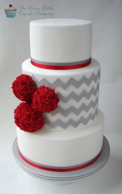 a grey and white wedding cake with chevron patterns, red ribbons and red pompoms