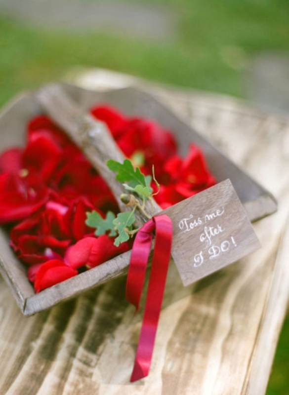 a wooden basket with red blooms, a red ribbona nd greenery on it is great for a little flower girl at your wedding