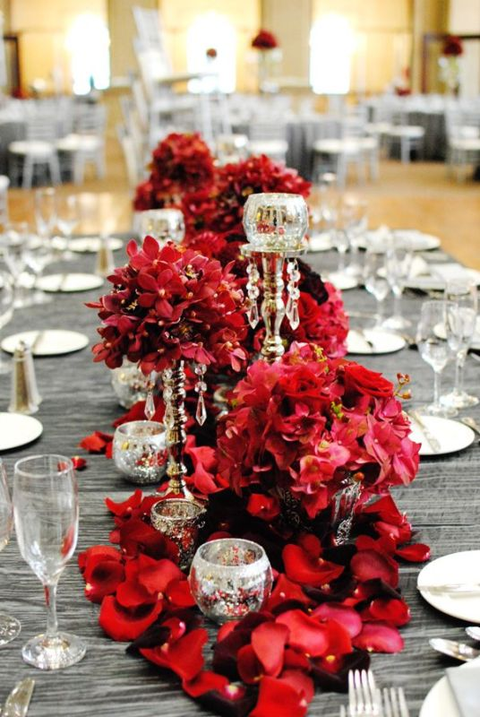 a shiny grey tablecloth and lush red florals plus crystals and mercury glass candleholders