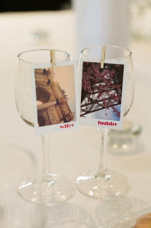 your wedding glasses accented with Polaroids from your favorite places is a very cute idea for a travel themed wedding