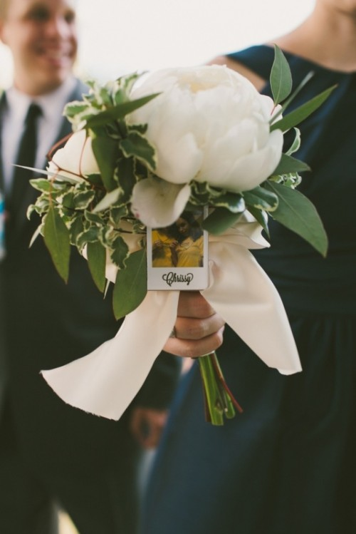 a bridesmaid bouquet with a Polaroid attached to find out where and whose bouquet is