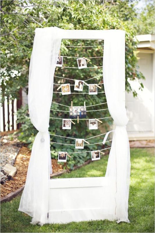 a cute wedding decoration of a frame with curtains and Polaroids hanging on the ropes