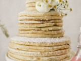 a pancake wedding cake with sugar powder and fresh white blooms is a fab idea for a modern laid-back wedding